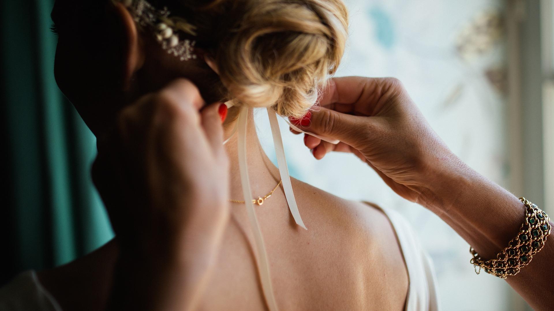 vrouw maakt het lint van een haar accessoire vast